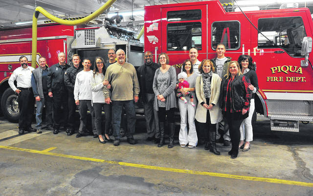 Mike Ullery | Daily Call Members of the Piqua Fire Department family pose for a photo with one of the department's engines, and retired NFL player and lung cancer awareness spokesperson Chris Draft, on Friday.