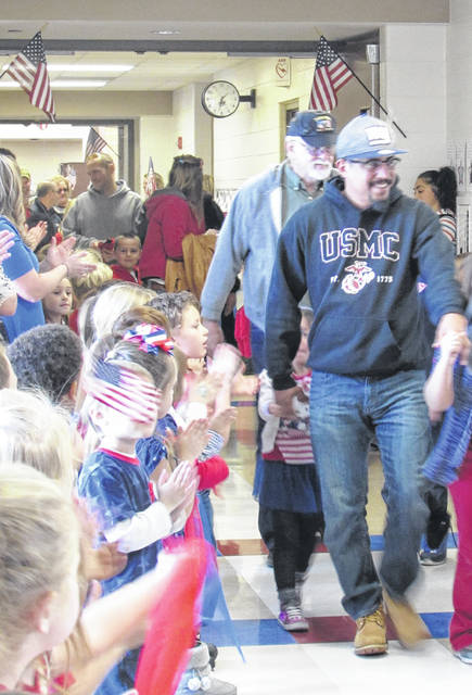 Sam Wildow | Daily Call Veterans are welcomed by a crowd of students and staff cheering them on as they walk through the first grade wing at Springcreek Primary Elementary School during the special Veterans Day ceremony held on Friday.