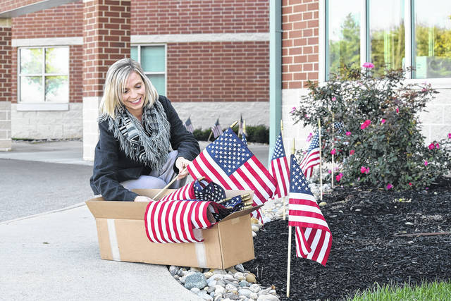 Provided photo UVMC Future Leaders co-chair Jenny Jones places memorial flags at the hospital in honor of veterans. The flags project is sponsored by the Future Leaders group and hospital administration.