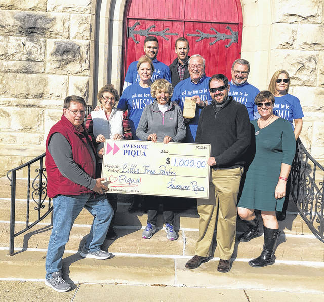 Provided photo St. James Episcopal Church received a grant for $1,000 from the Awesome Piqua Chapter of the Awesome Foundation on Nov. 14. Pictured are, front row, left to right: Barney Littlejohn, Marissa Littlejohn, Cindy Pearson, Rev. Robert Hill; second row, left to right: Margaret French, Dan French, Joe Hinds; Kazy Hinds; back row, left to right: Spencer Peltier, Jim McMaken.