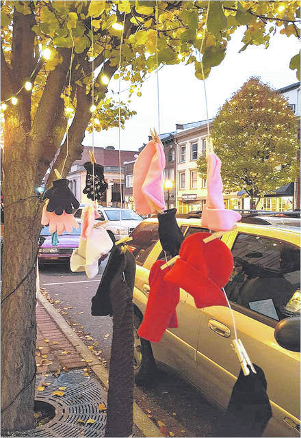 """Provided photo Visitors to downtown Piqua will see trees adorned with lights, as well as gloves, hats and scarves. St. James Episcopal Church knitting circle is responsible for the additional """"decorations"""" and hope that those in need will help themselves to the items."""