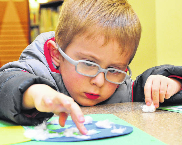 Dylan Coby, 3, of Troy works on a Christmas project, along with his mom Monday, in the children's area of the Piqua Public Library on Friday during Christmas on the Green.