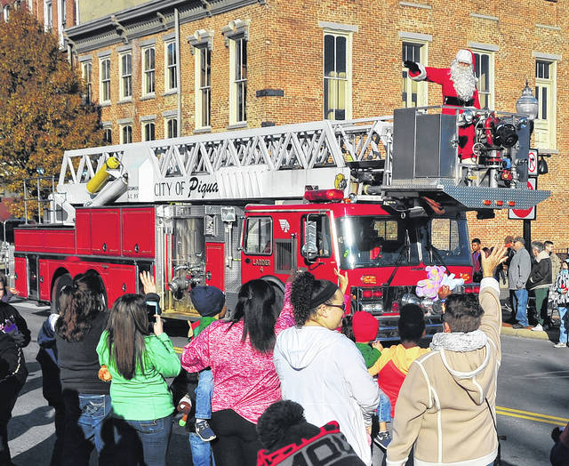 Mike Ullery | Daily Call Children of all ages greet Santa Claus as he comes to town on a Piqua Fire engine during Saturday's Mainstreet Piqua Downtown Christmas Parade.