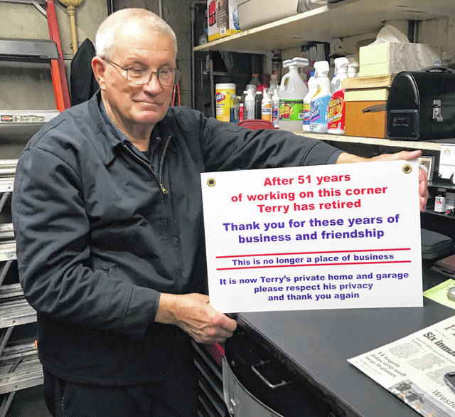 Terry Kinsinger, owner of Terry's Service Station at 500 W. High St., Piqua, holds the sign he placed in the window of his business at the end of the day on Thursday. Kinsinger is retiring after 51 years of servicing vehicles at that location.