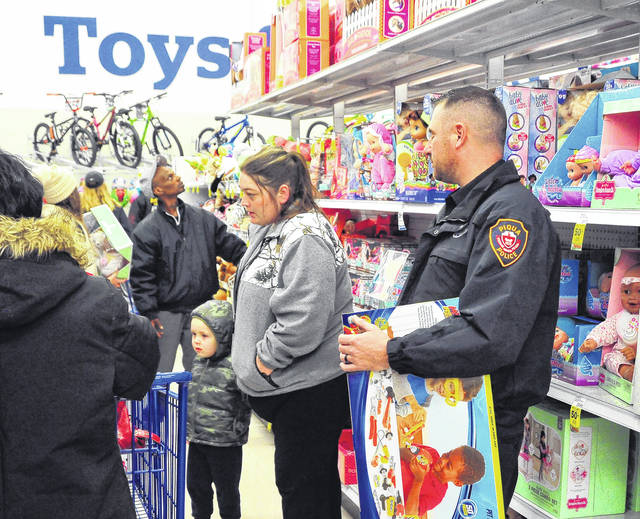 Mike Ullery | Daily Call Piqua police officer Jeremy Weber assists an area family in shopping for toys as part of the annual Shop With Cops sponsored by the Miami County FOP. The gifts will be delivered, along with food items, to homes next week.