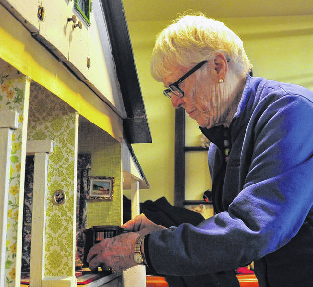 Mike Ullery   Daily Call Ann Wellmeier Hilliard of New York City places items in a large doll house that she donated to the Piqua Public Library.