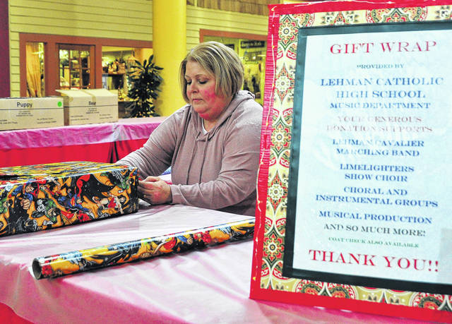 Mike Ullery | Daily Call Lehman parent Shelley VanSkiver of Sidney wraps gifts at the Lehman gift-wrapping booth at the Miami Valley Centre Mall of Friday. The annual fund-raising event at the mall helps provide funds for both the instrumental and vocal music department at Lehman High School.