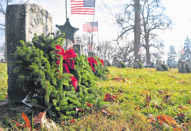 Mike Ullery | Daily Call Christmas wreaths adorn the graves of America's veterans buried at Forest Hill Union Cemetery in Piqua as the cemetery takes part in the Wreaths Across America event being held in cemeteries across the country. The cemetery, along with Jamison & Yannucci Funeral Home, placed wreaths on the graves on nearly 400 veterans on Saturday.