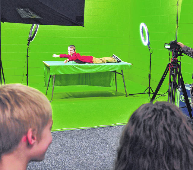 "Mike Ullery | Daily Call Kolin Noreikas ""swims"" against a green screen at Piqua High School on Wednesday. Noreikas, and third-grade classmates in Linda DeWeese's and Hope Davis' Washington Primary School classes are working with the Piqua High School Media Deapartment to create a video based on the book <em>The Miraculous Journey of Edward Tulane</em>, by Kate DiCamillo. Third-grade student actors were coached by PHS students Morgan Ford and Casey Graves."
