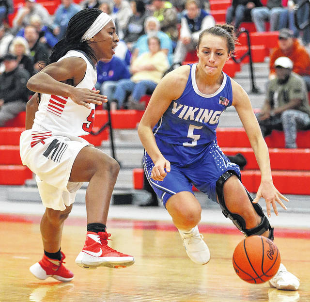 Photo courtesy Lee Woolery/Speedshot Photo Miami East's Morgan Haney drives around Troy's Valena Robinson Saturday at the Trojan Activities Center.