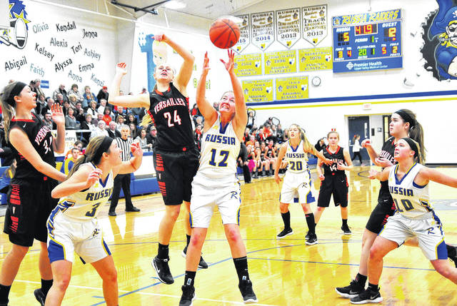 Versailles' Elizabeth Ording (24) and Russia's Cameo Wilson (12) battle for a rebound on Saturday at Russia High School.