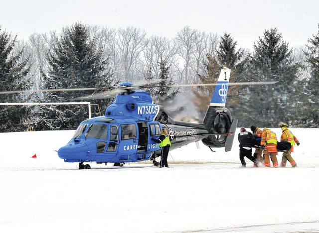 Mike Ullery | Daily Call Tipp City EMS and firefighters, along with CareFlight nurses, prepare to load a young patient about the medical helicopter at Kyle Park in Tipp City on Saturday following an ice rescue on a nearby pond after a sledding accident.