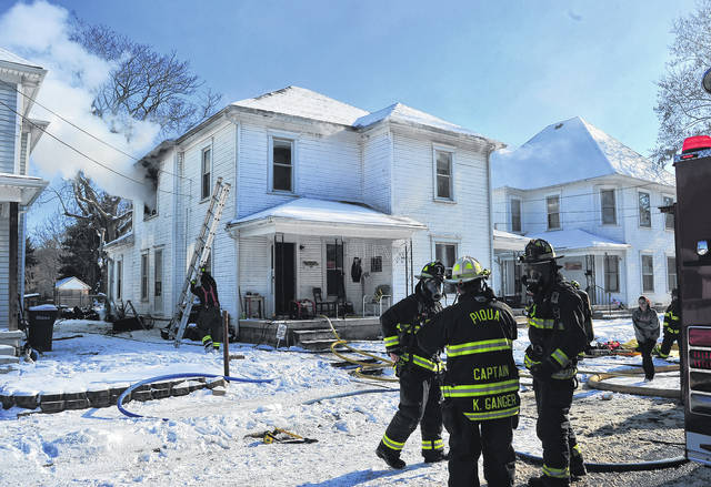 Mike Ullery | Daily Call Smoke pours from a second-floor window as firefighters from Piqua and Covington battle a New Year's Eve house fire at 117-119 Cleveland Street on Sunday.