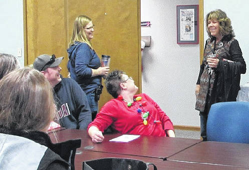 Sam Wildow | Daily Call Piqua City Schools Transporation Supervisor Beth Cain (back left) and other school bus drivers surprise retiring bus driver Cheryl Jones (back right), who retired on Friday after working the last 25 years as a bus driver for PCS.