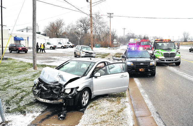 Mike Ullery | Daily Call Saturday's first snowfall of the season led to a number of crashes around the county, including this one on County Road 25-A north of Piqua, where a driver lost control near a slide-off that had occurred, striking the vehicle and a Piqua firefighter and his wife who were with the first vehicle. The firefighter was not injured. His wife was transported to Upper Valley Medical Center for treatment and released.
