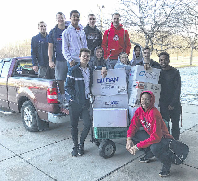 Provided photo The Piqua High School boys basketball team delivers boxes of items collected during their annual canned food drive. Pictured are: front center: Devon Brown; center row: Trevor Billet, Haden Schrubb, Cory Cotrell, Trey Richmond, Devin Fosler, Xian Harrison; back row: Holden Yount, Dylan Motter, Nick Rigolan Qurri Tucker, Ben Schmiesing.