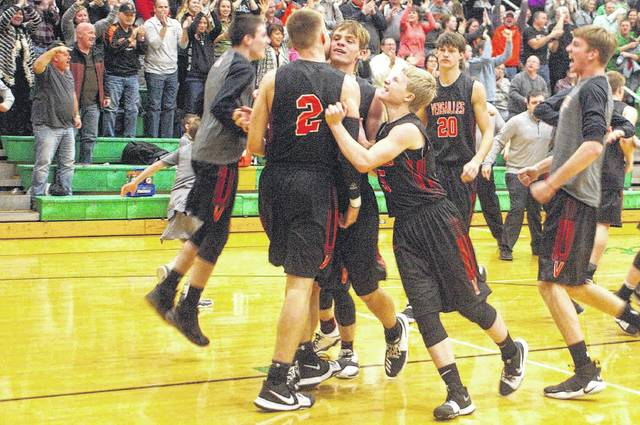 Kyle Shaner/Aim Media Photo Versailles celebrates after Justin Ahrens (2) made a game-winning shot at the buzzer to beat Anna Wednesday night.