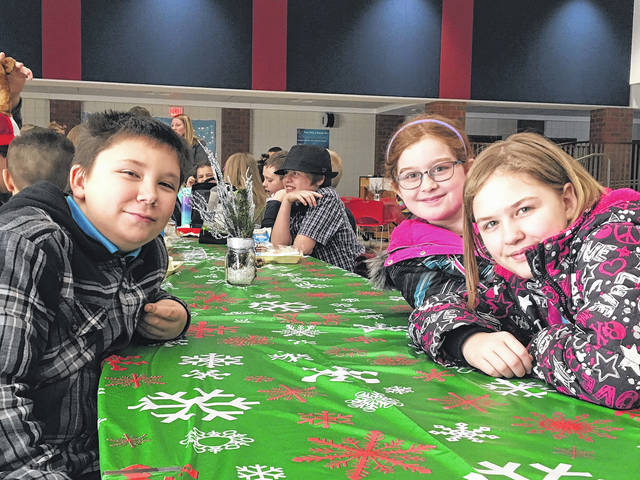 Sam Wildow | Daily Call Fourth grade students Benjamin Thompson, Ava Werst, and Grace Harshbarger enjoy lunch together at Wednesday's formal dining event at Piqua Central Intermediate School.