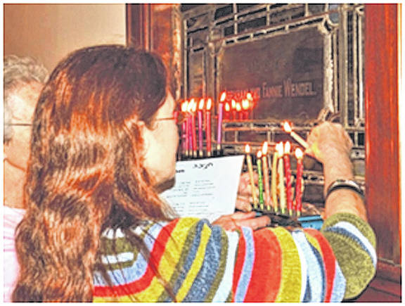 Provided photo A member of Congregation Anshe Emeth in Piqua lights the menorah during a past Hanukkah service. Hanukkah begins the eveninig of Tuesday, Dec. 12, and ends the evening of Wednesday, Dec. 20.