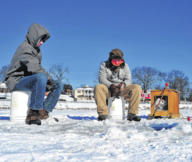 Mike Ullery | Daily Call Ethan Beeman, 15, of Covington, left, and Cordell Daugherty, 16, of Piqua brave sub-zero windchill to try their hand at ice fishing on Tuesday. Daugherty's grandfather Bill Hughes said the boys had been wanting to learn to ice fish so they went to Echo Lake to give it a try. The boys reported that the ice was around 7-8 inches thick and the fish were not cooperating.