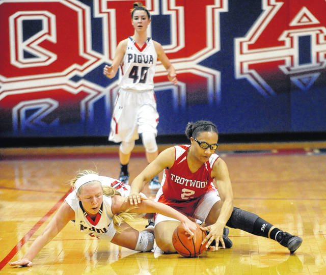 Mike Ullery | Daily Call Piqua's Lauren Williamsfig fights for a loose ball with Trotwood's Myla Barnes as Lily Stewart (40) races to assist Wednesday night.