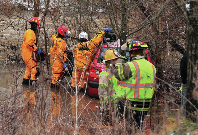 Mike Ullery | Daily Call Firefighters from West Milton work the scene of single-vehicle crash on State Route 55 at Elleman Road on Friday afternoon. The lone occupant of the vehicle died at the scene.