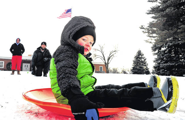 Mike Ullery | Daily Call Kevin Deaton, Jr., 4, slides down the hill at Mote Park on Tuesday afternoon as his mom and dad, Kevin and Jennifer, look on.