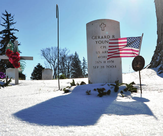 Mike Ullery | Daily Call A blanket of snow covers graves at Forest Hill Union Cemetery in Piqua on Thursday, including that of Korean War veteran Gerard R. Young. With temperatures forecast to be above freezing for the next few days, that snow blanket will, in all likelihood, give way to wet grass.