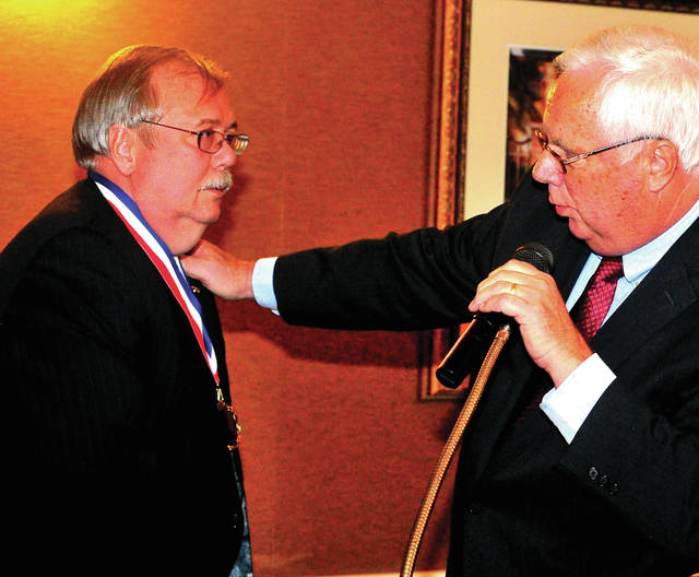 Mike Ullery | Daily Call  Mark Wion, left, is awarded the Piqua Area Chamber of Commerce 2017 Order of George by 2011 recipient Jim Hemmert during Thursday's 72 annual meeting and 51st Installation of the Order of George Award.