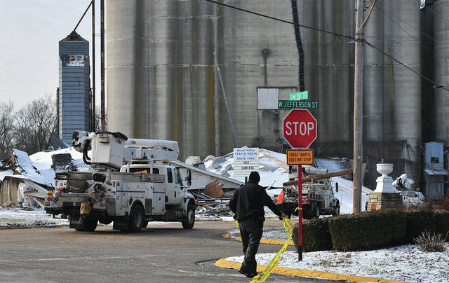 Mike Ullery | Daily Call A Clark Co. Sheriff's Deputy moves caution tape as a convoy of Dayton Power & Light vehicles arrives at Miami Valley Feed & Grain in New Carlisle on Thursday morning. All grain has been removed from St. Rt. 571 but much cleanup work and debris removal remains to be done. A deputy on the scene said that it is estimated that the highway will remain closed until January 31 due to safety concerns.