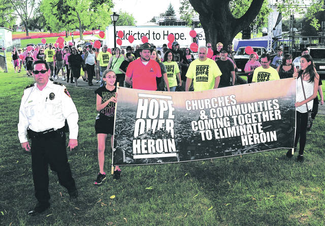 Mike Ullery | File photo Piqua Police Chief Bruce Jamison, left, leads the way in the 2017 Hope Over Heroin march through the streets of Piqua.