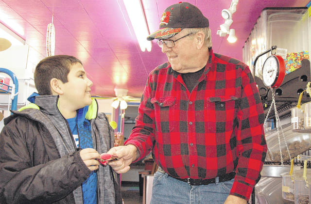 Cody Willoughby | Troy Daily News Candy on the Curve proprietor Richard Young offers a sample to Dominick Nealis, 9, of Piqua at the store on Friday. Richard and Lesley Young have recently announced Candy on the Curve's closing, tentatively set to shut its doors on Wednesday, Feb. 28.