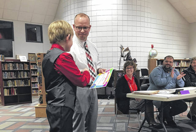 Sam Wildow | AIM Media Elementary School Principal Josh Long (right) congratulates fifth-grade student Jesse Harrison (left) on being recognized during the Covington Board of Education's student spotlight Thursday evening.