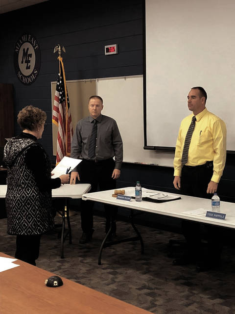 From left, Miami East Local Schools' treasurer Lisa Fahncke administers the oath of office to Mike Rindler and Brandon Fellers on Tuesday.