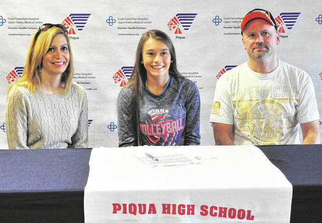 Mike Ullery/Call Photo Piqua High School senior Kelsey Peters signs her letter of intent to play volleyball for Edison State Community College. With Peters are her parents Paula and Randy Peters.