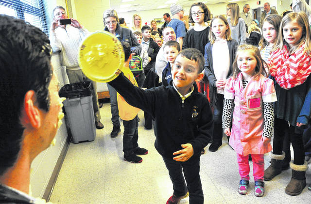 Mike Ullery | Daily Call Piqua Catholic School Principal Brad Zimmerman winces as kindergartener Wade Uhlenbrach tosses a pie during a Catholic Schools Week fundraiser on Thursday.