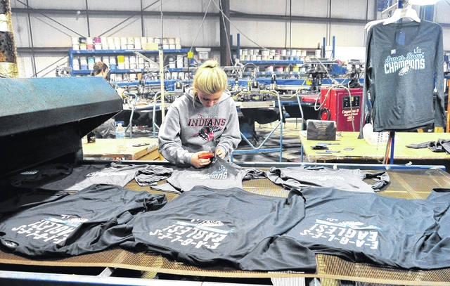 Mike Ullery | Daily Call Korren Evans puts labels on Super Bowl T-shirts at Atlantis Sportswear in Piqua on Wednesday. Atlantis Sportswear has been busy since the end of the Super Bowl, printing Philadelphia Eagles Super Bowl Champions shirts. Evans, from Piqua is part of the Upper Valley Career Center's School-to-Apprenticeship Program. She attends Upper Valley Career Center for half of each day before going to Atlantis Sportswear where she works the second half.
