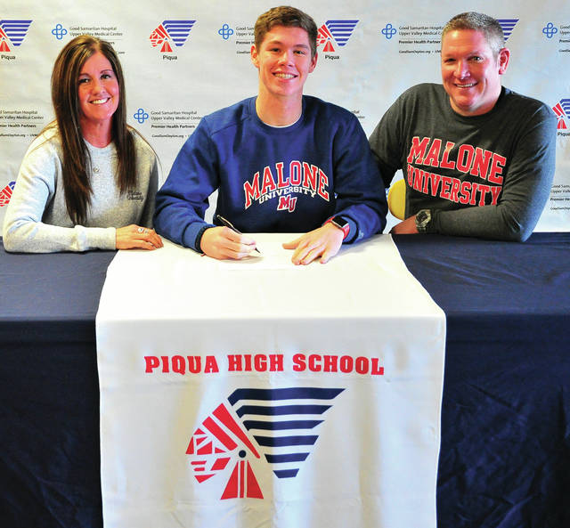 Mike Ullery | Daily Call Piqua High School senior Hayden Schrubb signed his letter of intent to play football for Malone University. With him are his mom Liz and his dad Aaron.