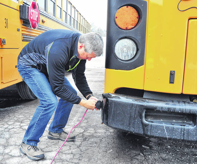 Mike Ullery | Daily Call Todd Wion connects a power cord to his Piqua City Schools' bus at the end of his route on Thursday to insure it is ready to roll on Friday morning. Keeping the diesel engines warm overnight is especially important during winter. Wion has been working some 39 years in the education system. His wife, Lois, is secretary at Piqua Central Intermediate School.