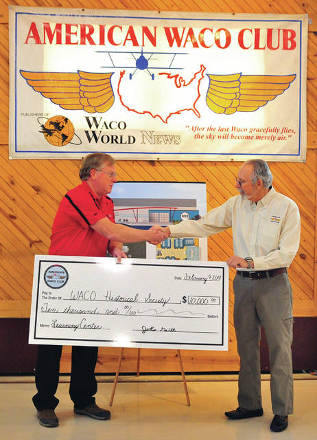 John Gerth, right, president of the American WACO Club, based in Indianapolis, presents a check in the amount of $10,000, to WACO Historical Society President John Schilling during a ceremony at the WACO Museum and Learning Center in Troy on Friday.