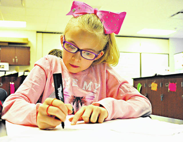 Mike Ullery | Daily Call Kayleigh Stover begins the task of decorating the costume that she will wear when she and her fourth-grade classmates from Piqua Central Intermediate School attend the annual Hug The Earth Festival at Stillwater Prairie in May. Naturalists from the Miami County Park District were at PCIS on Wednesday to work with students on learning about the environment and creating costumes.