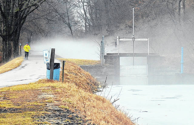 Mike Ullery | Daily Call A lone runner emerges from fog created by warmer temperatures and melting ice on the hydraulic canal near Swift Run Lake on Thursday morning.