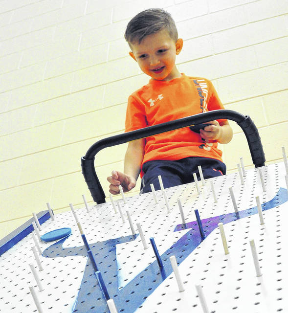 Mike Ullery | Daily Call Hudson Bowman, 4, tries his luck at Plinko during Saturday's Viking Fest fundraiser at Miami East