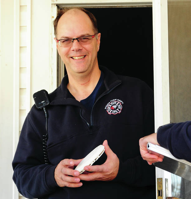 Mike Ullery | Daily Call file photo Piqua firefighter Bob Bloom emerges from a home on Harrison Street carrying a carbon monoxide (CO) alarm in November 2016. The Piqua Fire Department responded to the home on a report of a CO alarm sounding. The home was evacuated until firefighters determined that it was safe to re-enter.