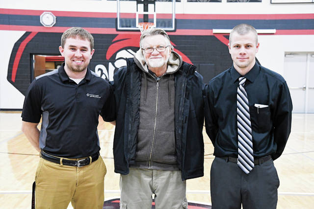 Provided photo Kerry Freeman, center, thanks Brian Downs, left, and Brandon Studebaker, right, for saving his life after he collapsed during a basketball game at Covington High School in December. Downs is an athletic trainer for the UVMC Center for Sports Medicine, and Studebaker, is an assistant basketball coach and paramedic on the Covington fire and rescue squad.