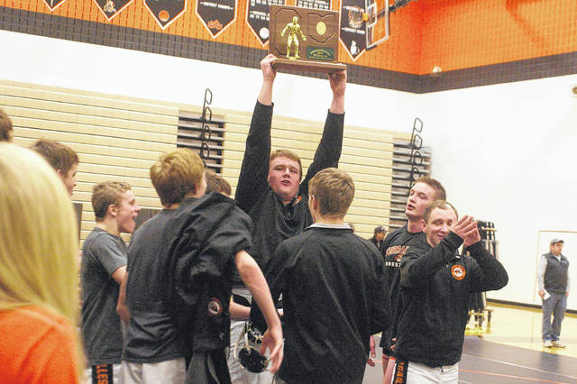 Kyle Shaner/Aim Media Photo Versailles senior Jeffrey Ware holds up the trophy after the Tigers won the OHSAA Regional State Duals championship last week.