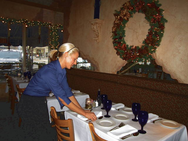 Troy Daily News file photo Former server Nicole Barney prepares one of the tables at La Piazza for dinner.