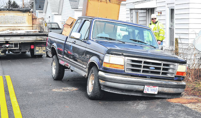 Mike Ullery | Daily Call Piqua officials examine a sink hole that caused concern on Commercial Street on Thursday. A pickup truck parked over a storm sewer fell up to its front axle when the storm sewer beneath it collapsed around 12:30 p.m. City officials said that recent rains weakened the 15-inch storm sewer that runs under Commercial Avenue, causing the collapse. Commercial Avenue, between Miami Street and Young Streets will remain closed until Piqua officials can evaluate damage and repair the storm sewer. The truck that fell into the opening in the storm sewer was winched out of the hole. There were no injuries.