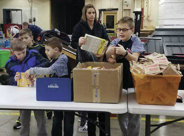 Provided photo Piqua Braves members, from left to right, Dane Funderburg, Landon Sullenberger, Aiden Penrod and Grady Stillwell, help pack food for the Piqua Lunch Bunch Back Pack Program receently.