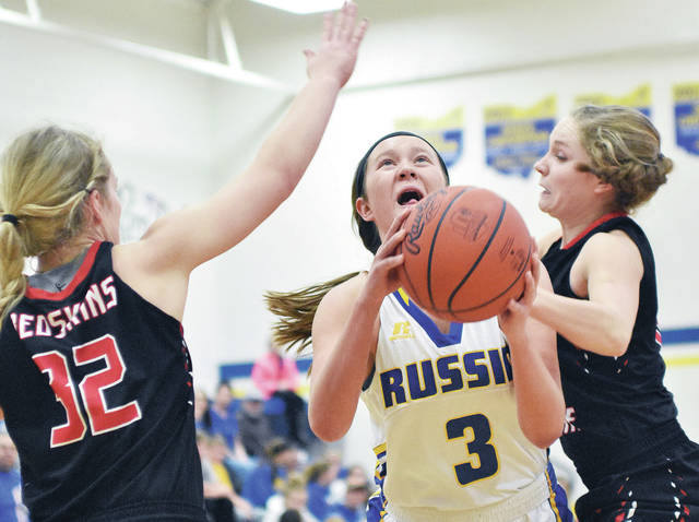 Luke Gronneberg/Aim Media Photo Russia's Jenna Cordonnier drives between Fort Loramie's Hattie Meyer (left) and Kennedi Gephart at Russia High School Thursday.